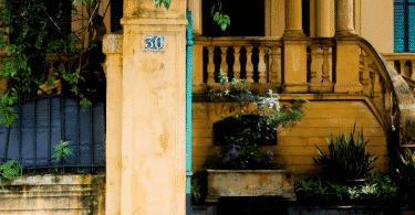 Foto da fachada de uma casa de muro amarelo