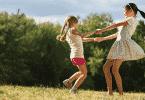 Duas meninas felizes dançando ciranda no parque