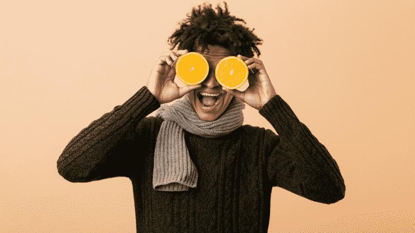 Homem sorridente segurando duas metades de laranjas na frente dos olhos