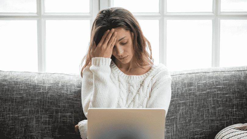 Mulher preocupada com computador no colo