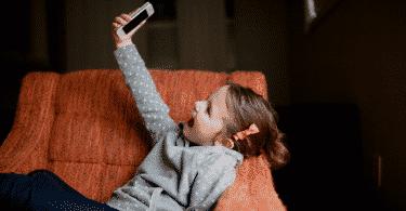 Criança deitada no sofá sorrindo tirando uma selfie