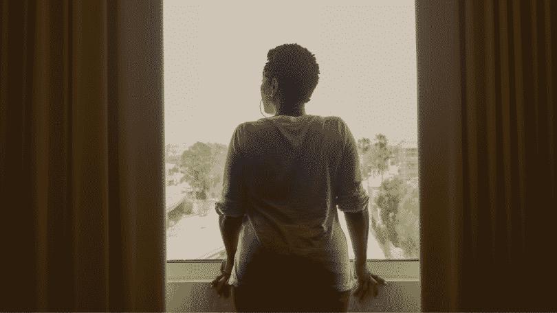Mulher olhando pensativa pela janela
