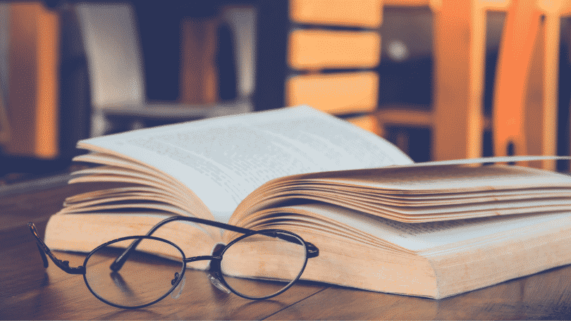 Livros abertos sob a mesa com óculos de leitura ao lado