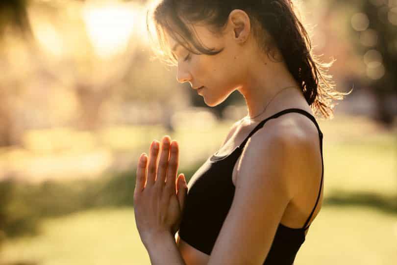 Mulher branca com as mãos juntas e cabeça baixa meditando.