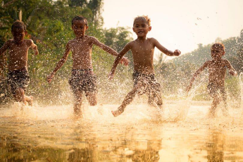 Meninos brincando em um lago.