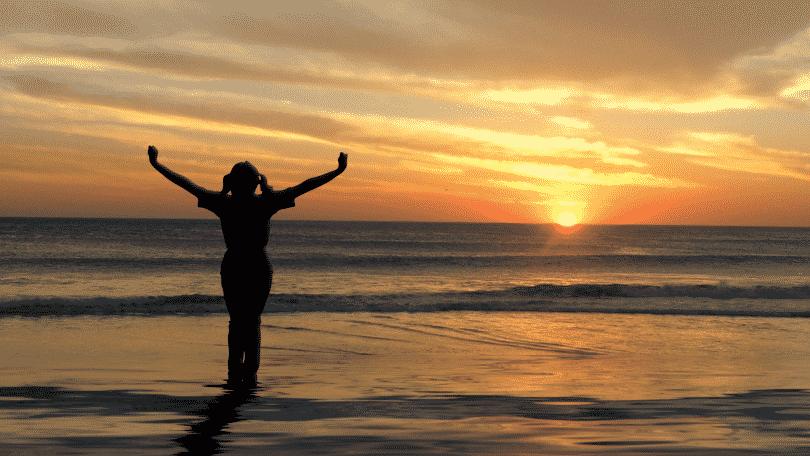Silhueta de mulher com braços abertos observando o por do sol na praia
