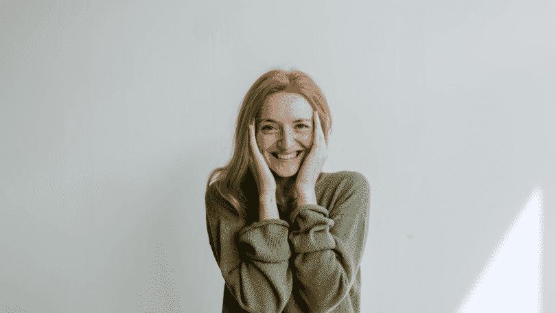 Mulher sorrindo com as mãos no rosto