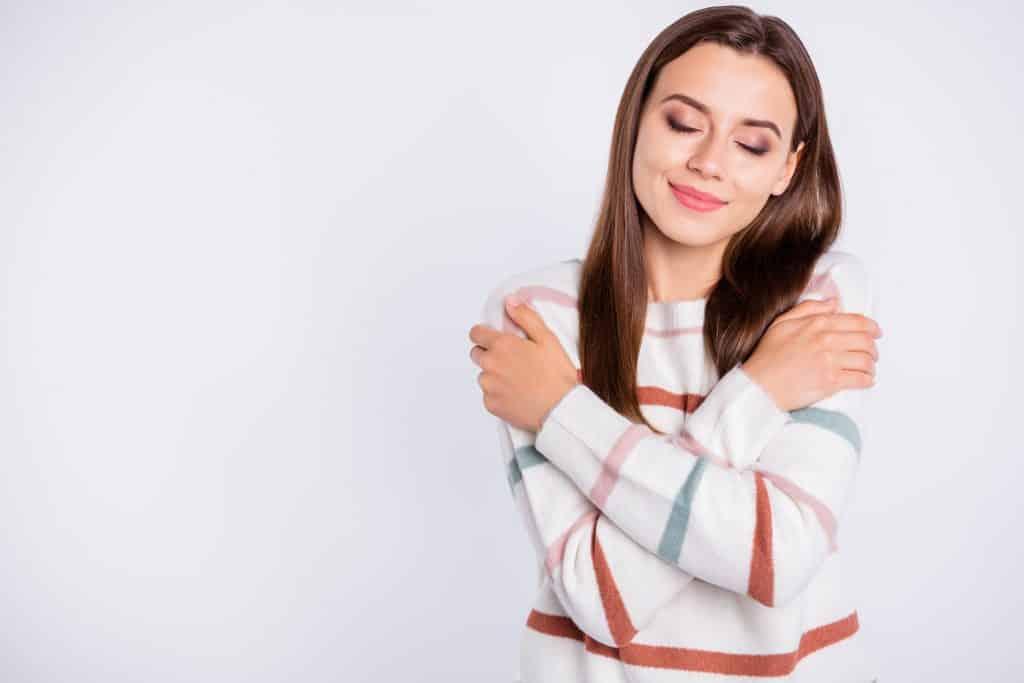 Foto de uma moça muito feliz se abraçando