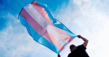 Um jovem caucasiano, visto de trás, segurando uma bandeira do orgulho sobre a cabeça contra o céu azul