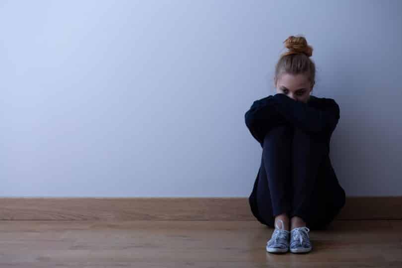 Mulher jovem com transtorno de ansiedade, vestindo roupas escuras, sentada no chão,