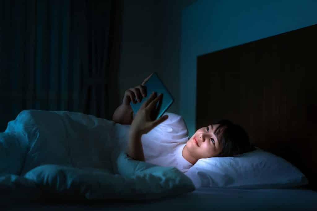 Mulher em celular assistindo a um vídeo antes de dormir