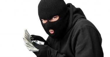 Conceito de ganância. Criminoso mal-humorado disfarçado segurando um monte de dólares roubados, isolado no fundo branco do estúdio