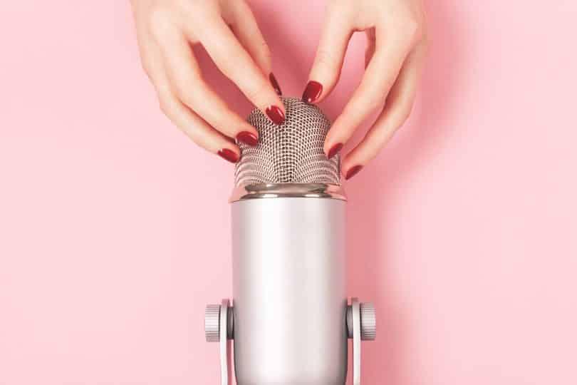 Mão de uma mulher com manicure perfeita perto do microfone está prestes a fazer batidas de unha. Fazendo sons ASMR. Gatilhos para relaxamento, boa noite de sono e alívio do estresse.