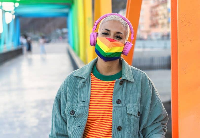 Mulher usando máscara colorida da bandeira LGBTQIA+