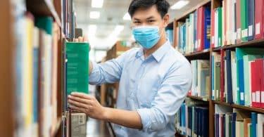 Homem asiático em uma biblioteca.