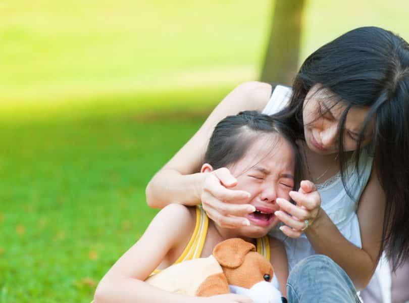 Mulher acalmando sua filha que está chorando.