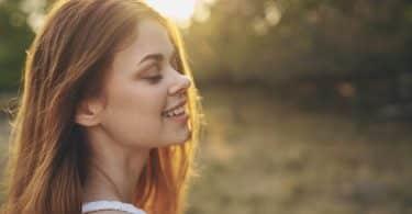Mulher branca sorrindo com os olhos fechados.