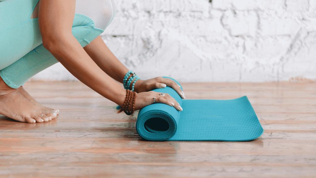 Pessoa desenrolando o tapete de yoga