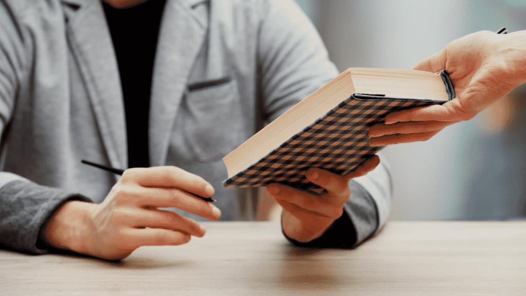 Leitor entregando livro em sessão de autógrafo para escritor sentado na mesa
