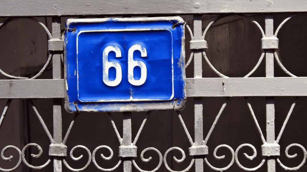 Placa azul no portão de uma casa com o número 66