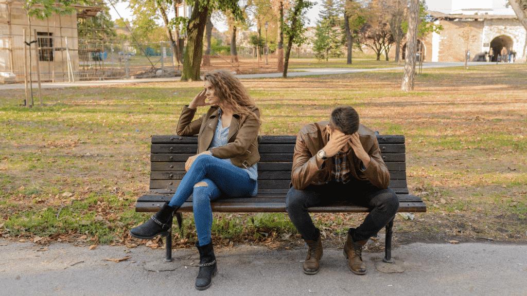 Casal brigado sentado no banco da praça
