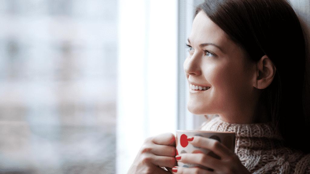 Mulher sorridente olhando pela janela segurando xícara de café