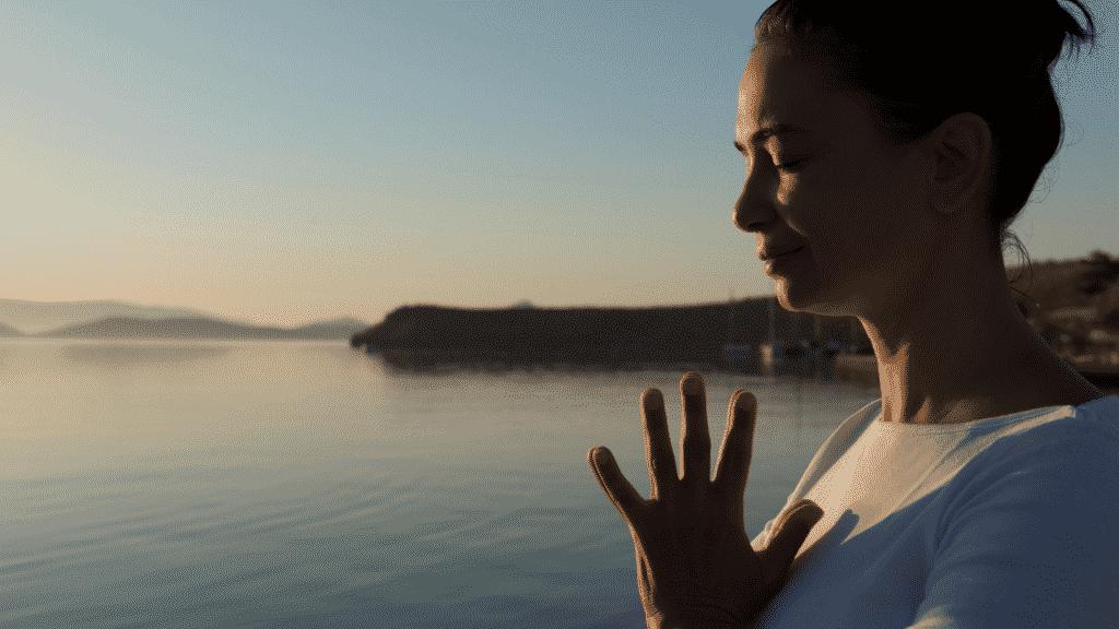 mulher de olhos fechados meditando na praia