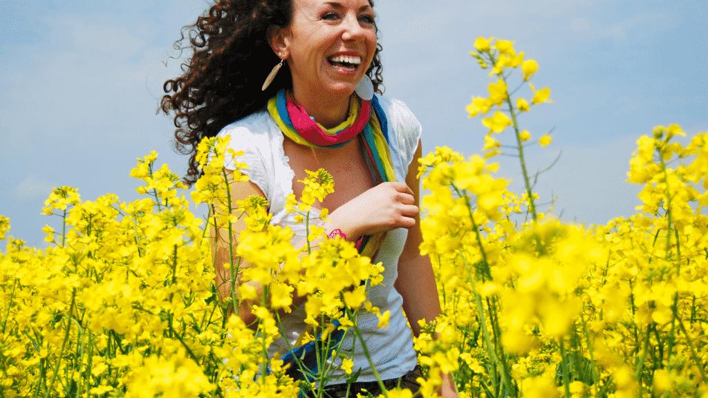Mulher sorrindo passeando pelo campo de flores