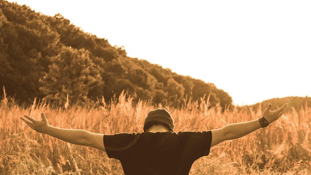 Homem de braços abertos no campo
