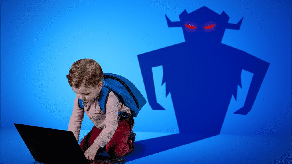 Criança mexendo no computador, este que fazer a sombra na parede que ilustra um monstro
