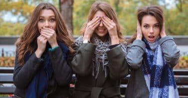 Mulheres brancas sentadas com as mãos na boca, olhos e orelhas.