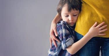 Menino abraçando a mãe.