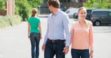 Jovem caminhando com a namorada na rua, olhando para outra mulher