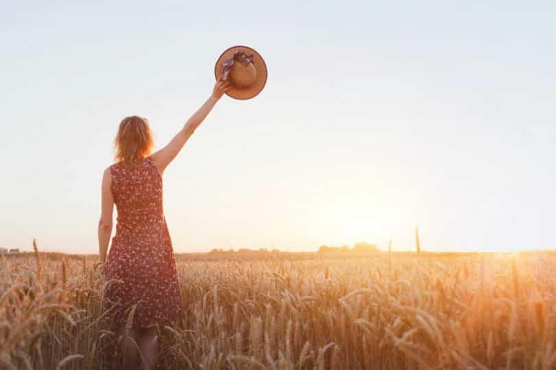 Mulher em um campo com uma mão levantada, segurando chapéu