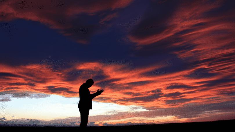 Homem com as mãos levantadas para o céu