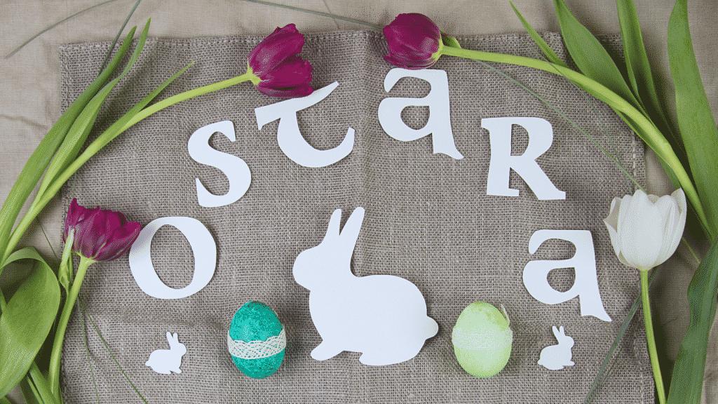 Celebração para Ostara com flores, ovos coloridos e recortes em formato de lebre