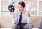 Homem sentado segurando duas máscaras, uma branca e outra preta
