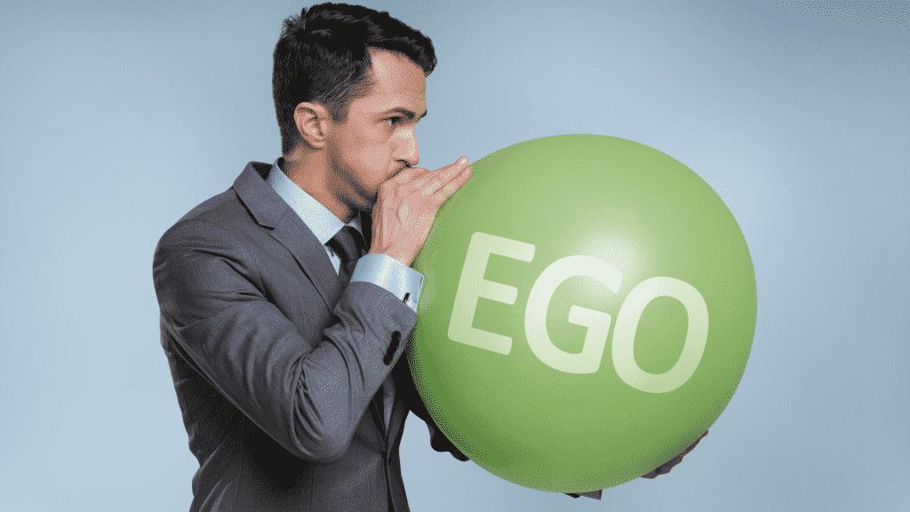 """Homem enchendo balão de ar, onde está escrito """"ego"""""""
