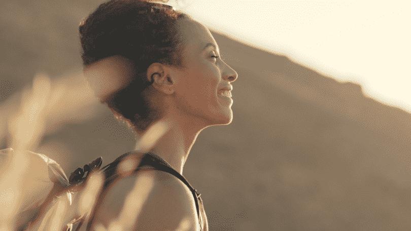 Mulher sorrindo de olhos fechados, com a luz do sol batendo em seu rosto