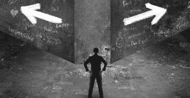 Homem parado, escolhendo entre dois caminhos para seguir