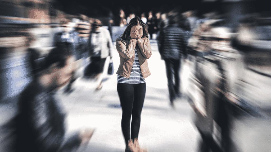 Mulher parada com as mão no rosto, no meio de uma multidão