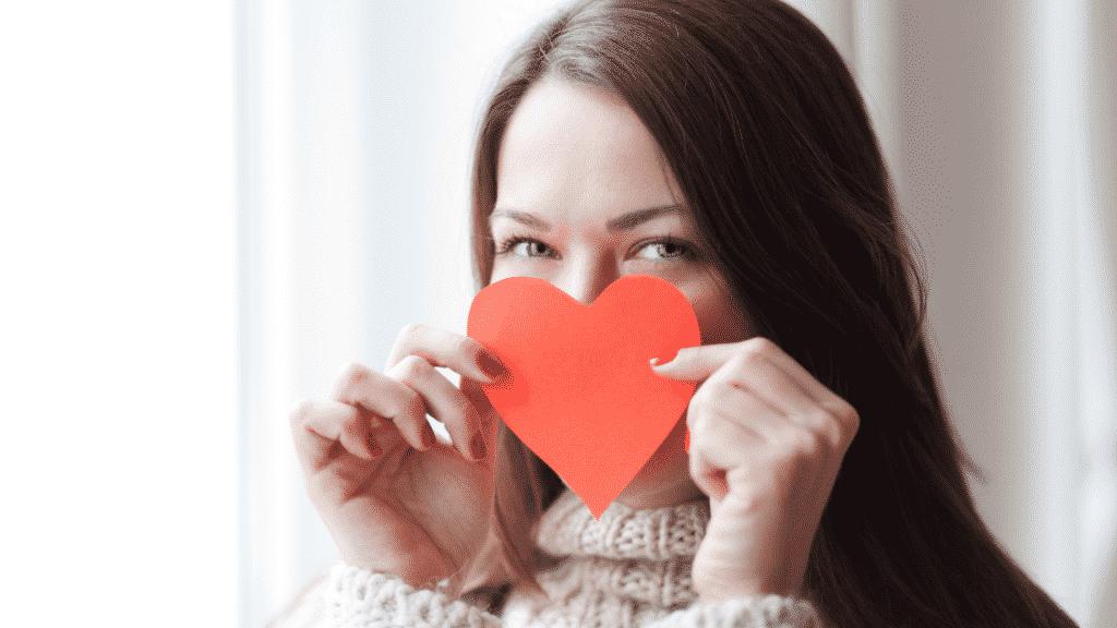 Mulher segurando um coração de papel sobre o rosto