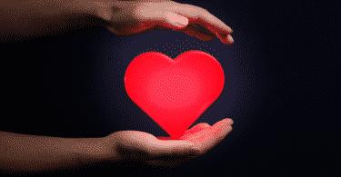 Coração vermelho entre as mãos de uma pessoa