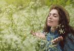 Mulher de olhos fechados em um campo, sentindo o aroma das flores