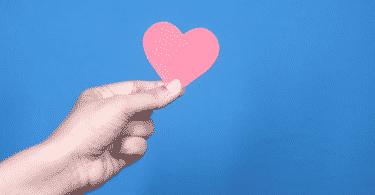 Imagem de uma mão segurando um coração de papel