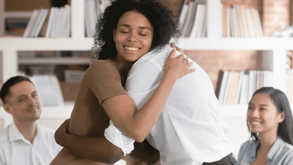 Mulher sorrindo e abraçando um homem. Ao fundo, pessoas observam e sorriem