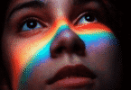 Rosto de uma mulher olhando para o alto. As cores da bandeira LGBTQIA+ estão refletidas em seu rosto