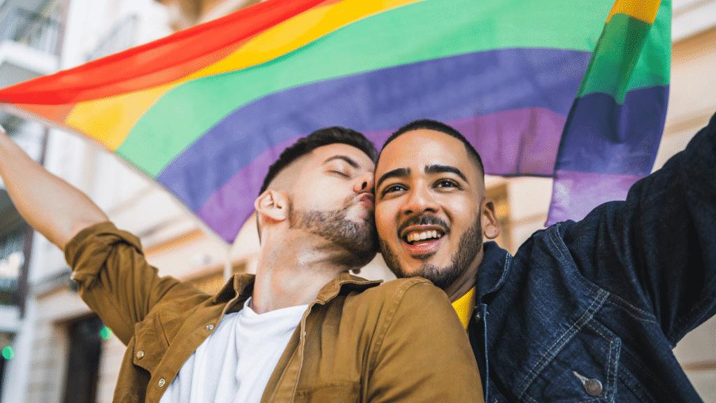 Casal gay segurando a bandeira LGBTQIA+. Um deles está beijando o parceiro no rosto