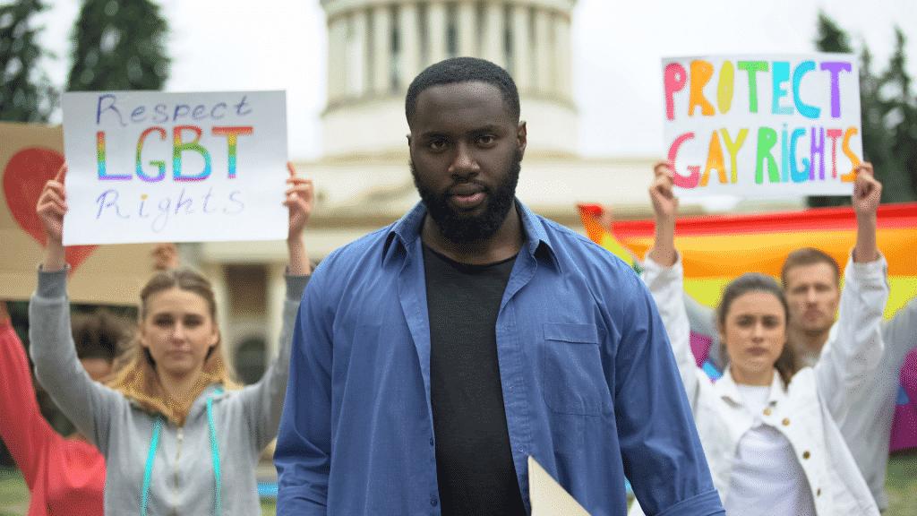 Homem e mulheres em uma passeata segurando placas, pedindo respeito e proteção aos direitos LGBTQIA+