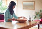 Mulher arrumando um ornamento em cima da mesa de madeira
